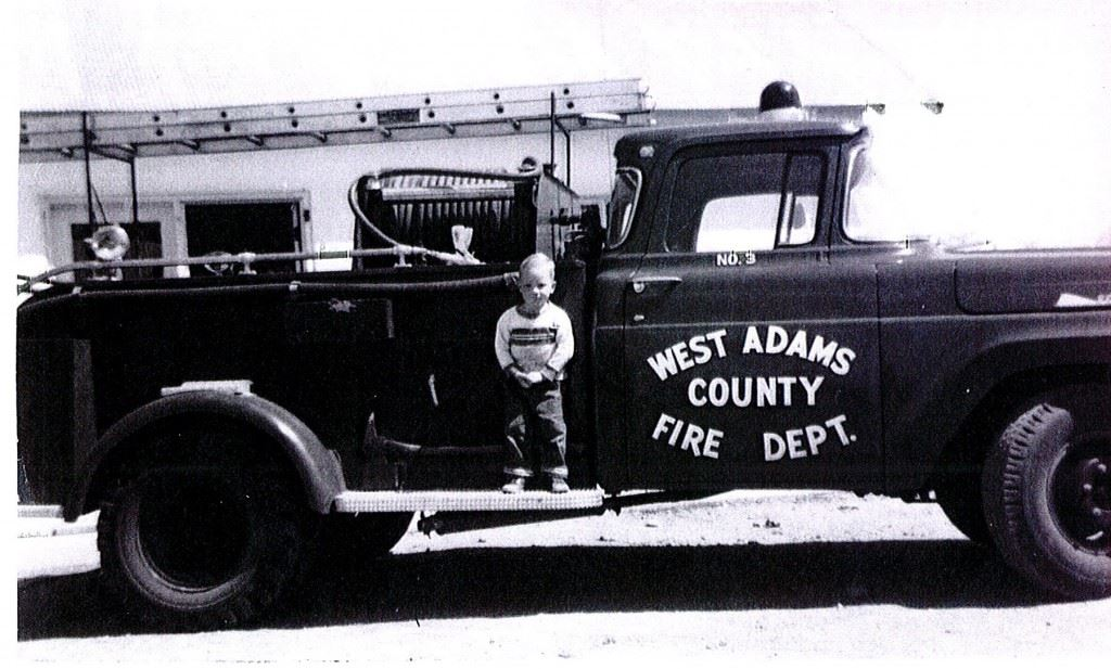 Black and White Photo of Little Boy on Fire Truck