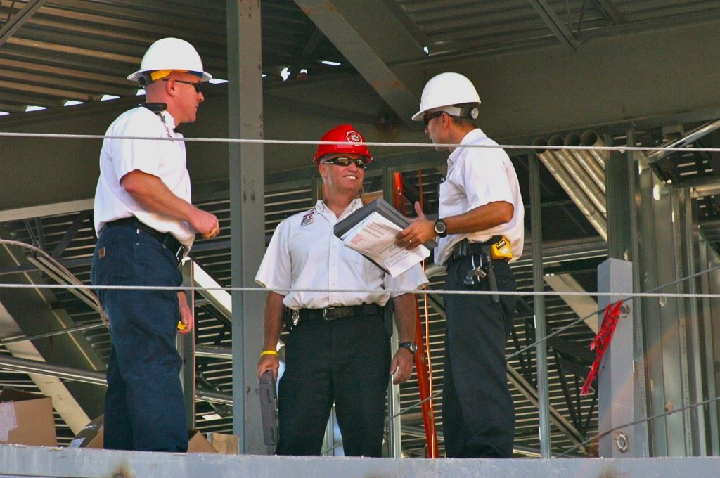 3 Men with Hard Hats Talking on Construction Site