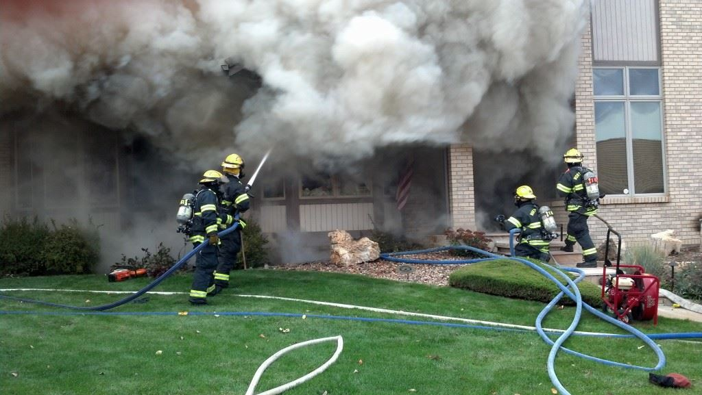 Fire Fighters Spraying Water on Smoking House