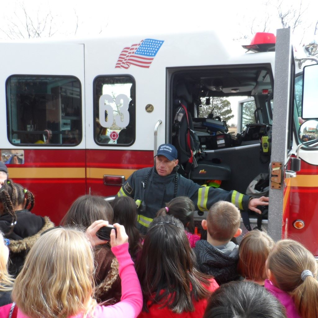 Fire Fighter Showing Fire Truck to Group of Kids