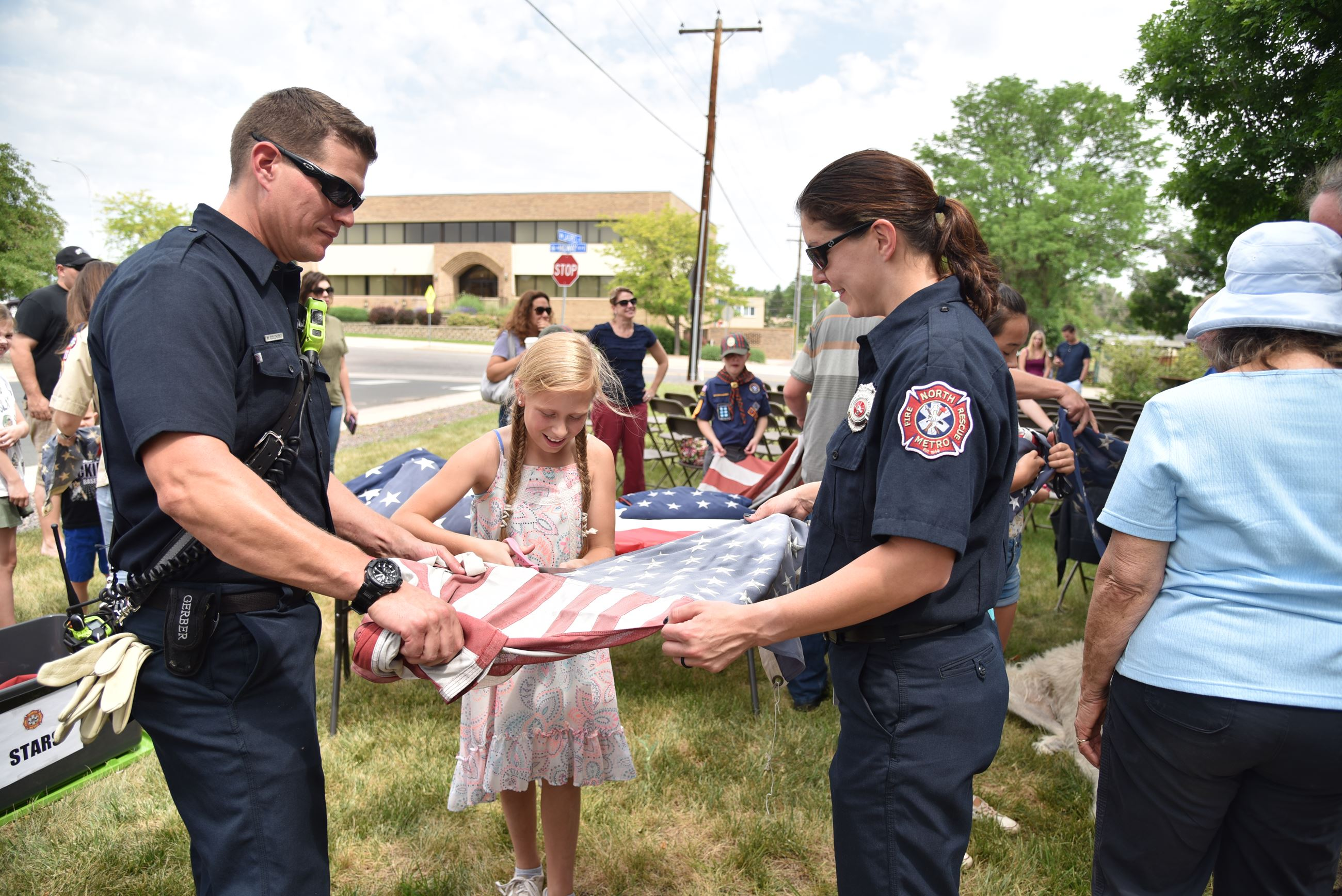 Young girl is assisted by two North Metro firefighters as she cuts the flag to properly retire it