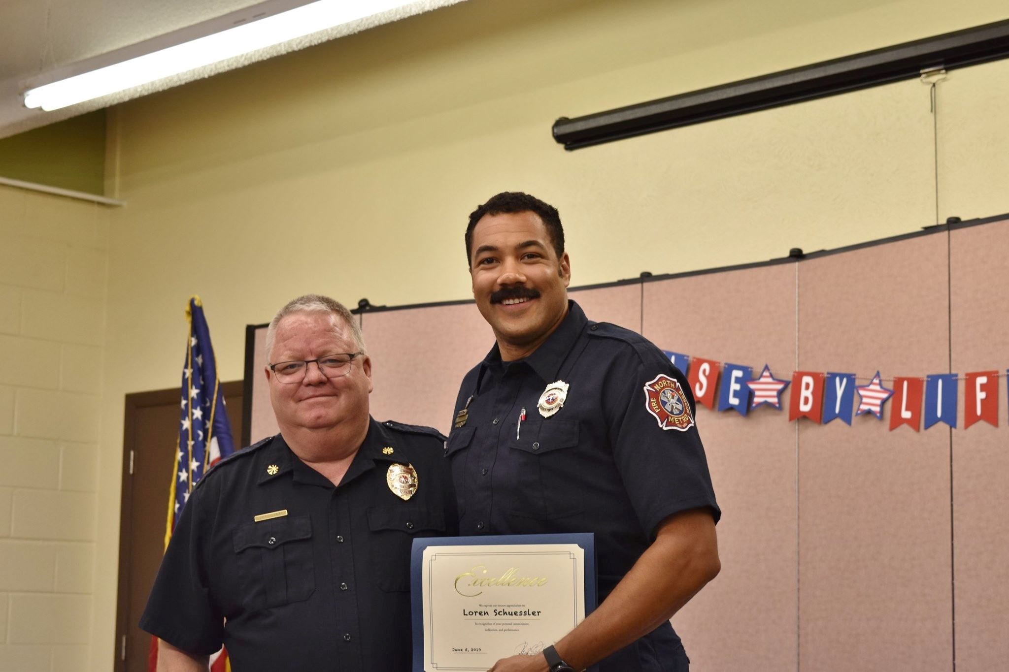 Division Chief Bybee awards Firefighter Schuessler with the Optimist Club Award