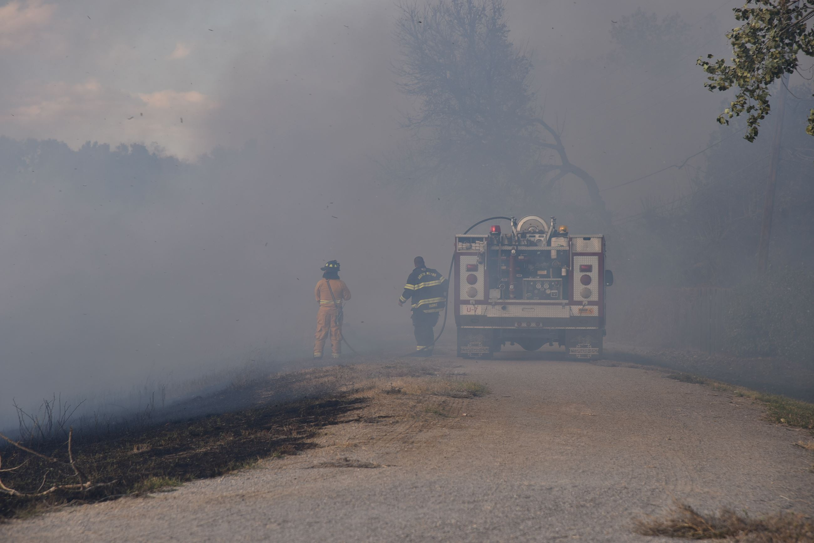 Firefighters use the assistance of a wildland brush truck to help extinguish flames of a grass fire