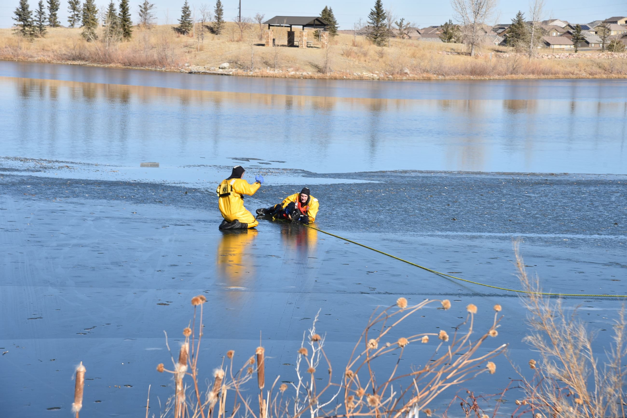 An officer trains a new firefighter on how to rescue a victim who has fallen through the ice.