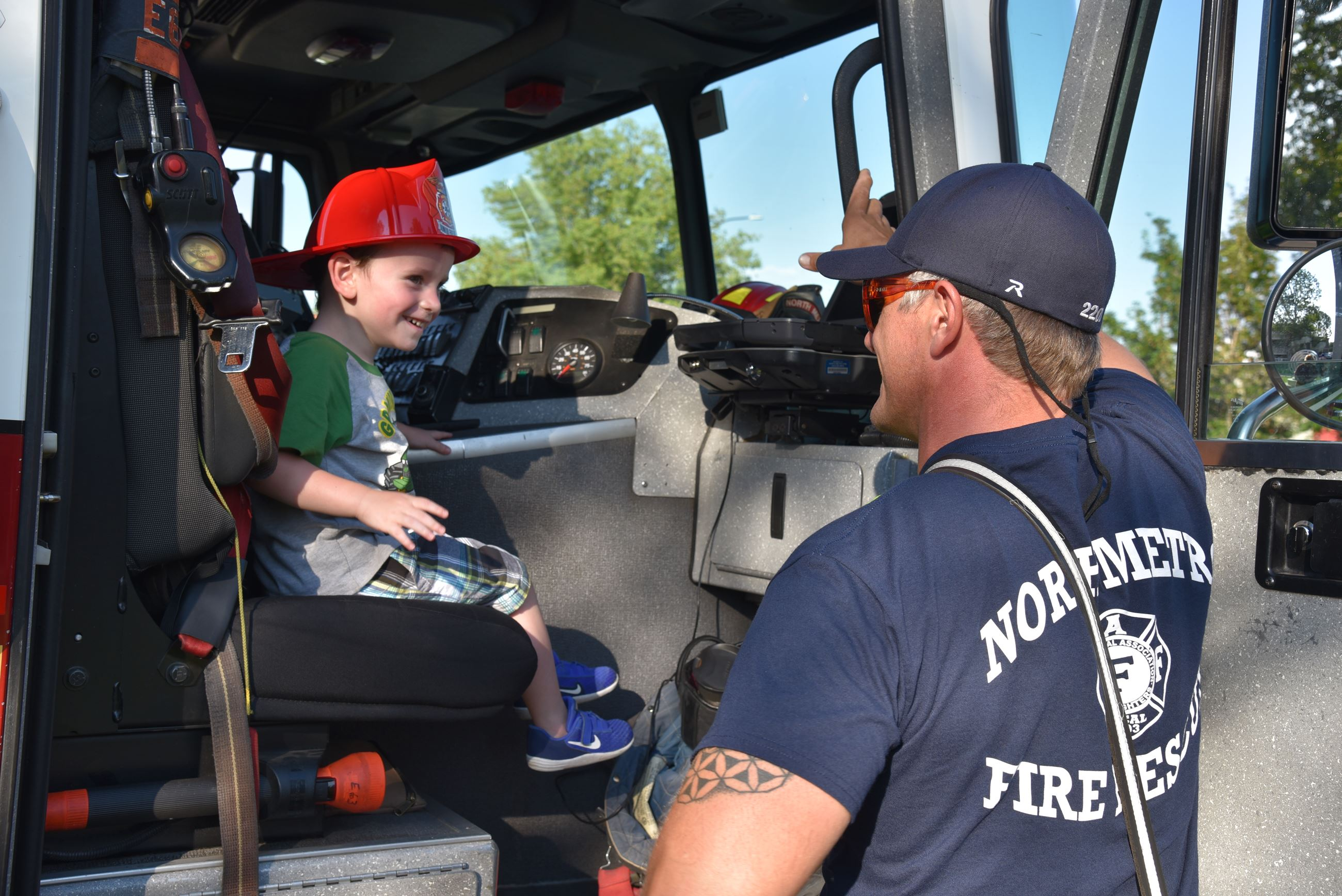 Firefighter giving engine tour to child