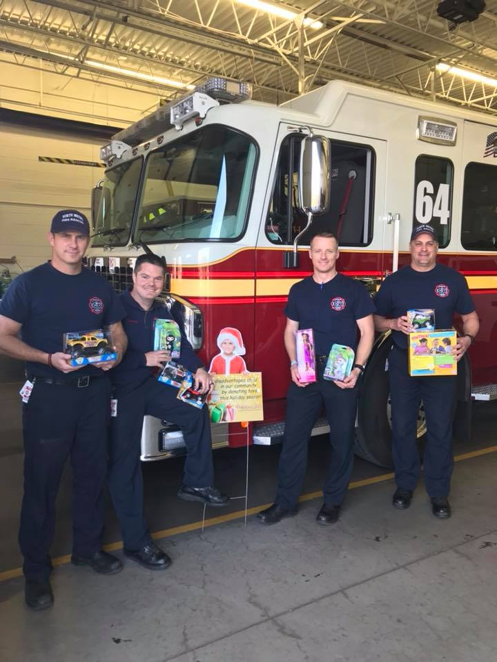 A crew holds up some toys donated to A Precious Child