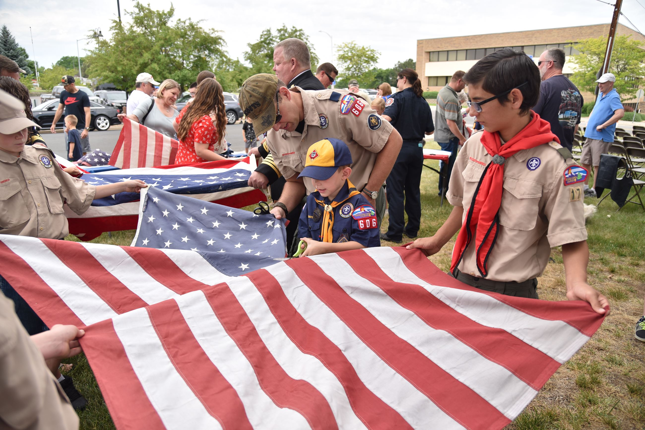 A group of Boy Scouts assist one another in cutting up the flag for proper retirement