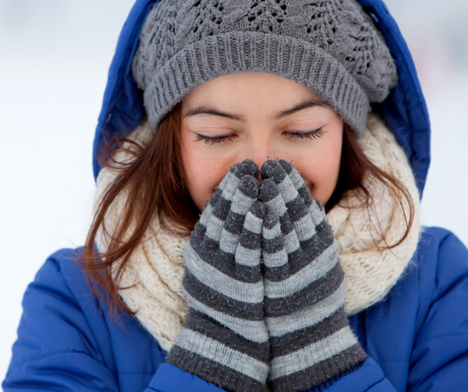 Person who is outside and dressed up in winter gear with mittens held up to her face