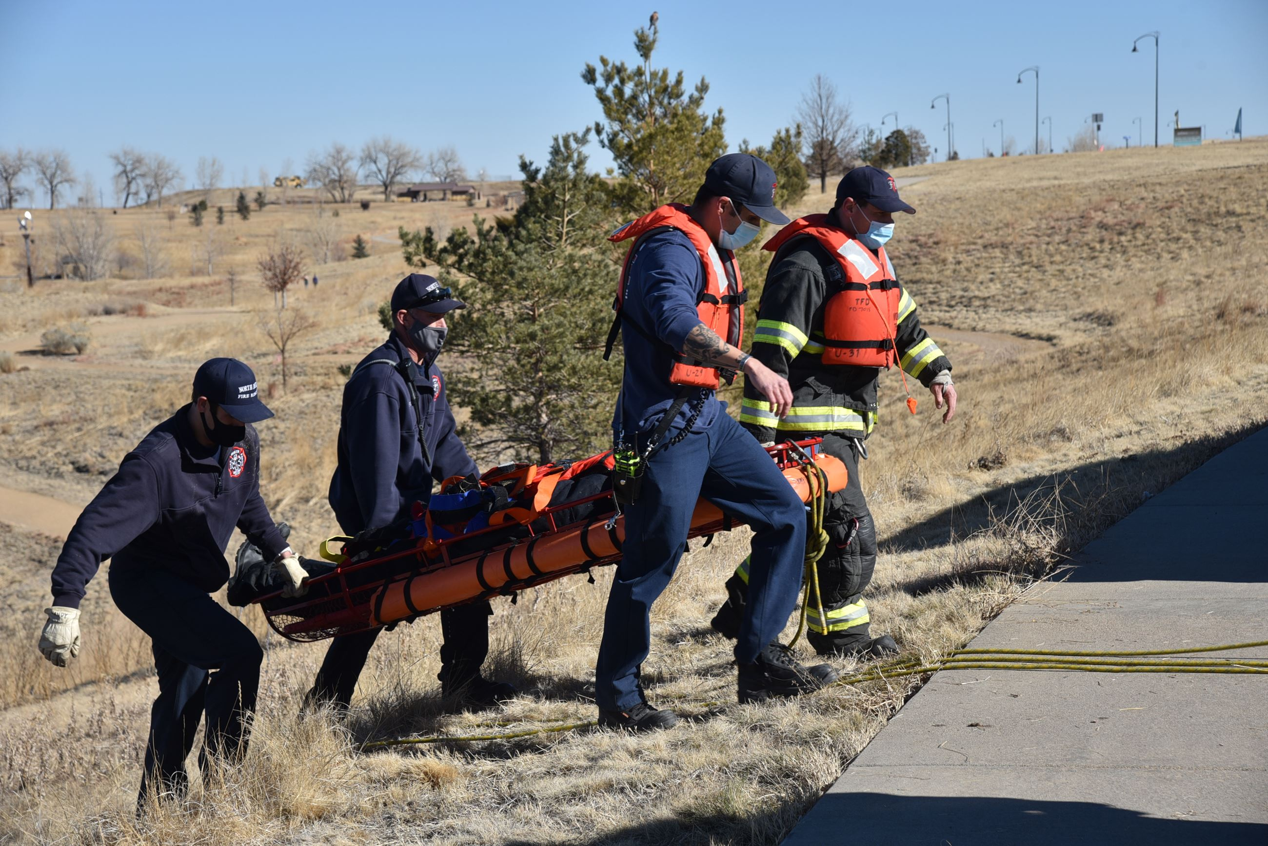 Firefighters transport the pretend victim up a steep incline to the medic unit.